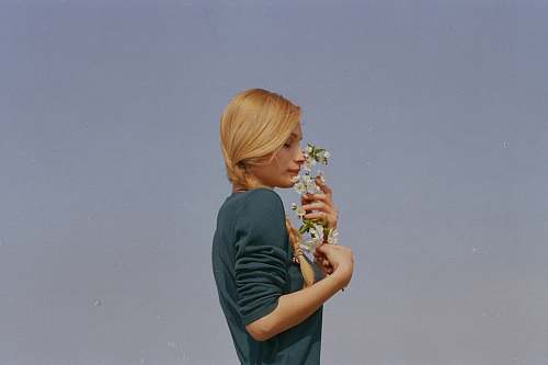 human woman smelling white petaled flowers person