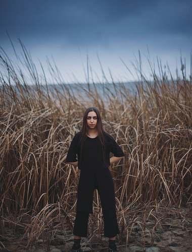person woman standing near brown grass field human