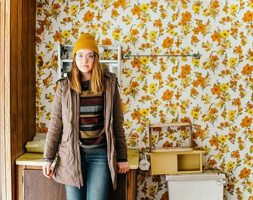 human woman standing near cabinet in front of floral wallpaper person