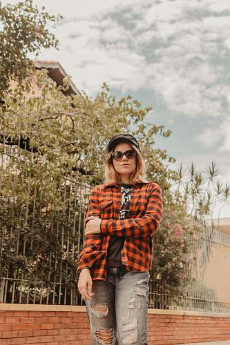 human woman standing near fence while posing person