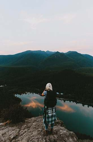 human woman standing on cliff taking picture of mountain person