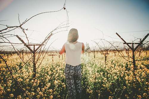 human woman standing on ground and surrounded by flowers person