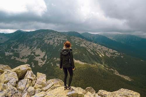 mountain woman standing on rock facing mountains mountain range