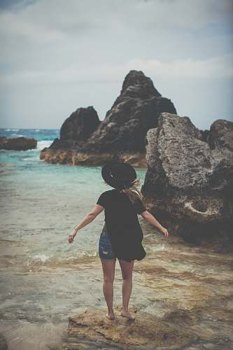 human woman standing on rock near ocean shoreline person