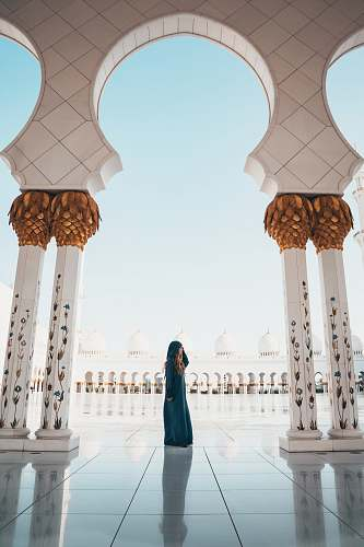 person woman standing on white tiled floor in the middle of concrete pillars building