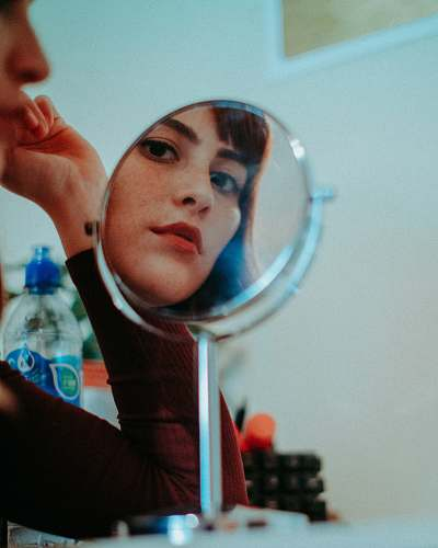 person woman staring at round mirror with silver frame human