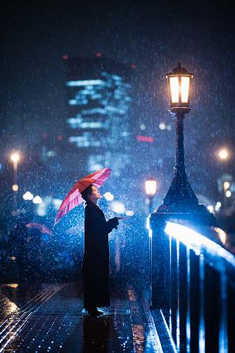 person woman using umbrella standing near bridge light post human