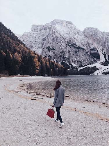 person woman walking beside body of water toward snow covered mountain during daytime mountain