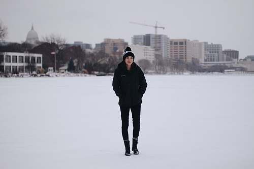 human woman walking on field with snow and bulidings person
