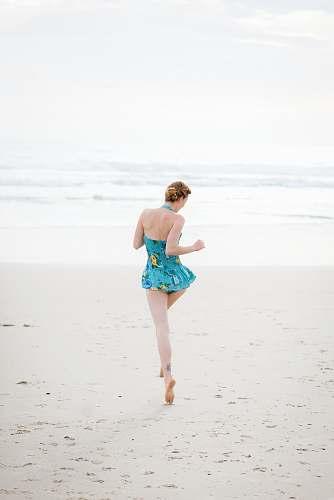human woman walking on shore near beach beach