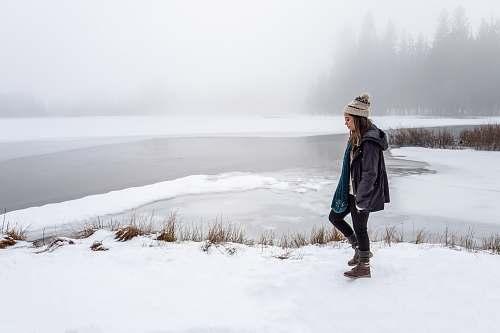 person woman wearing black jacket walking on snow human