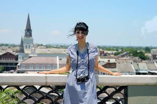 human woman wearing blue dress standing beside stand spire