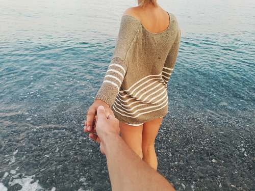 human woman wearing gray and white striped sweater walking on beach follow me photography person