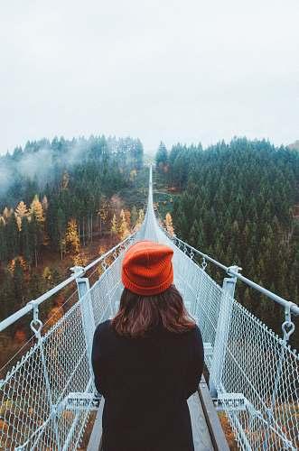 human woman wearing knit cap walking on white bridge between trees during daytime bridge