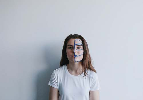 human woman wearing white crew-neck t-shirt with mask on face leaning on wall person