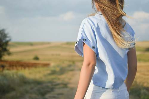human woman wearing white dress shirt standing on green grass field during day time person