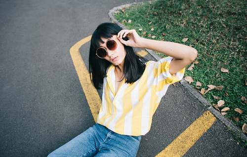 person woman wearing yellow and white striped collared shirt holding round-shaped brown sunglasses sitting on gray concrete pavement during daytime human