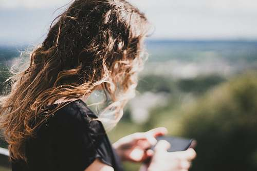 human woman with long curly blonde hair using smartphone person