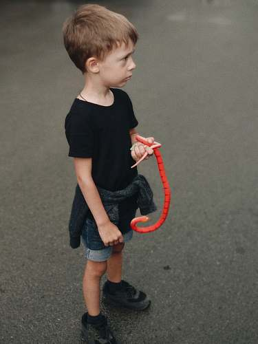 human boy holding red snake toy people