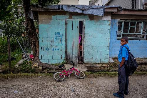 human boy standing in front of door near bicycle people