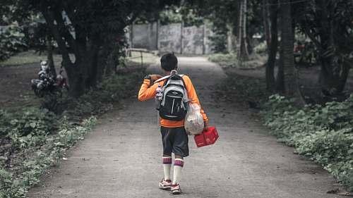 people boy with backpack walking on pathway between trees human