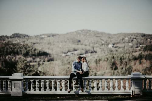human couple sitting on ledge in distant of mountain people