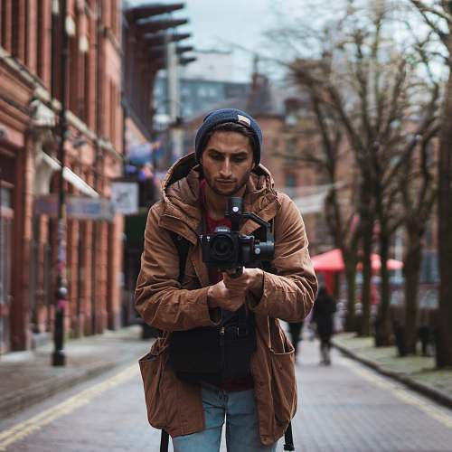 human depth of field photography of man holding camera people