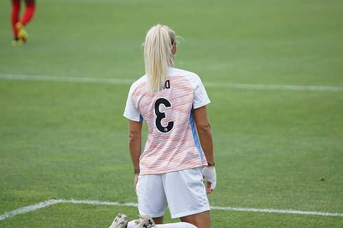 human female soccer player standing at field people