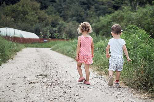 human girl and boy walking on the side of the road people
