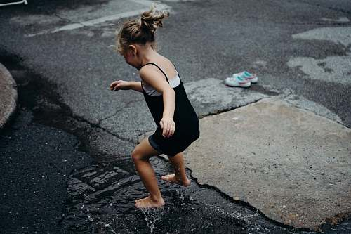 people girl jumps in the water surface on asphalt road during daytime human