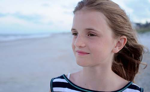 people girl standing at beach wearing white, green, and black striped shirt facing left side human