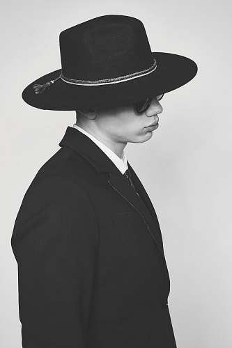 black-and-white grayscale photo of person's blazer hat