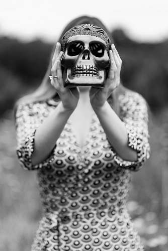 people grayscale photography of woman holding skull figurine black-and-white
