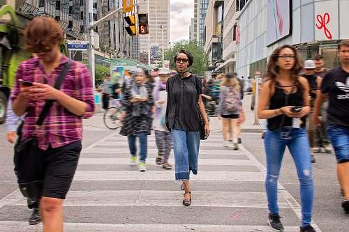 human group of people passing through pedestrian lane during daytime people