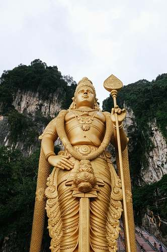 people low angle photograph of Lord Murugan state near mountain cliff under cloudy sky human