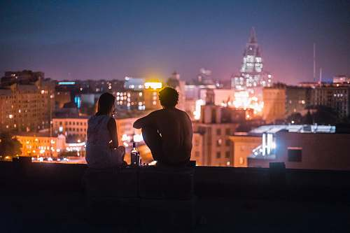 people man and woman chilling on rooftop in front of high-rise buildings human