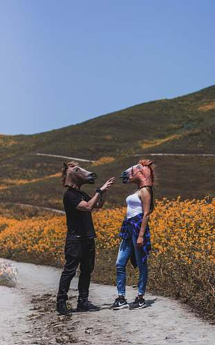 human man and woman facing each other while wearing horse masks near flower field during daytime people