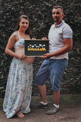 people man and woman holding manuela signage during daytime human