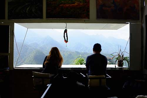 people man and woman inside room in front of window seeing mountains human