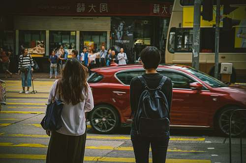 people man and woman standing near red car human