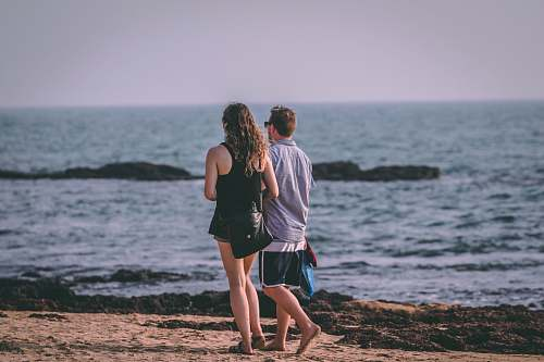 human man and woman walking by the beach during daytime people