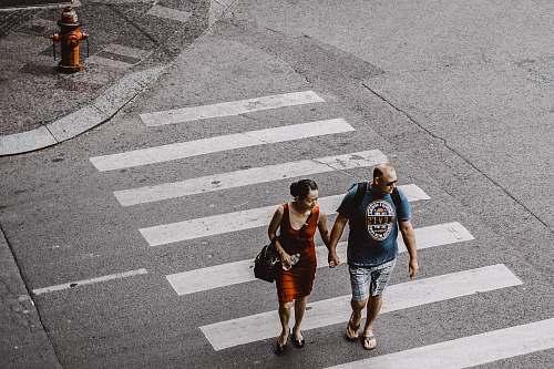 human man and woman walking on pedestrian lane during daytime people