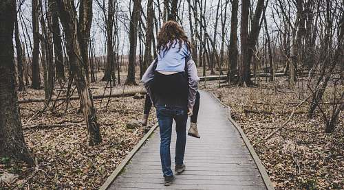 people man carrying a woman on his back in forest path human