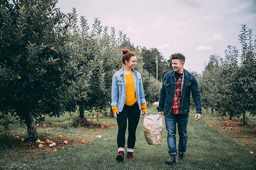 human man carrying bag with woman in fruit tree orchard at daytime people