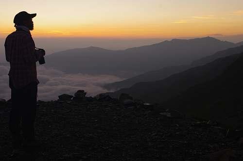 human man carrying camera facing sideways looking at the mountain range people