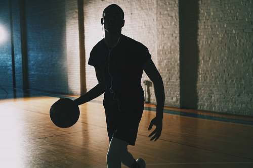 human man dribbling ball in closed basketball court people