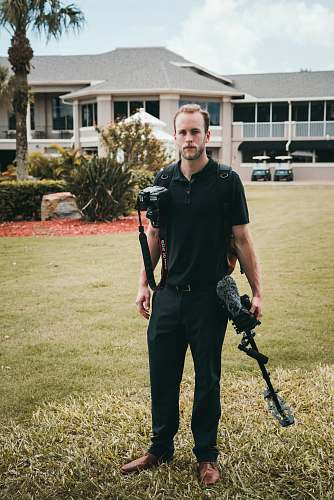 people man holding black glide cam and black Canon DSLR camera human