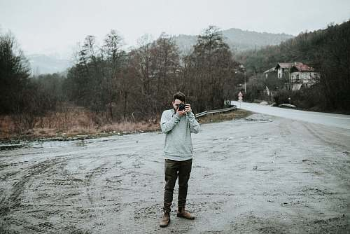 photographer man holding camera in snow-covered road people