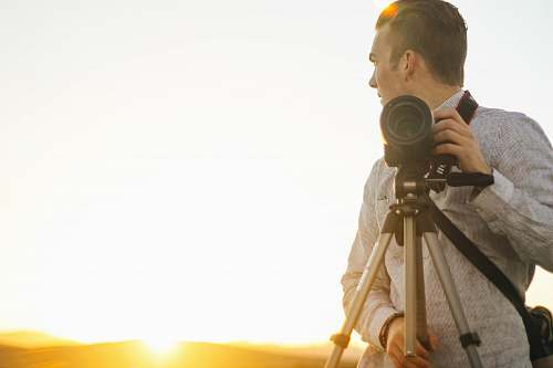 people man holding DSLR camera during golden hour human