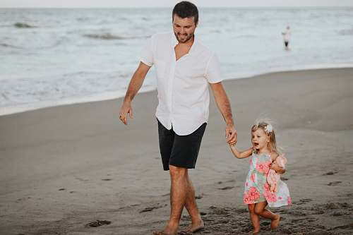 people man holding her daughter while walking at the coastline beach
